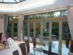 144 - Bifolding doors in a charcoal grey spray finish along with French doors with floating mullion to the left hand side